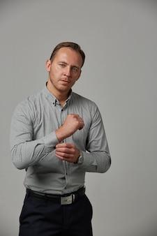 Jovem elegante com uma camisa cinza apertando os botões de punho