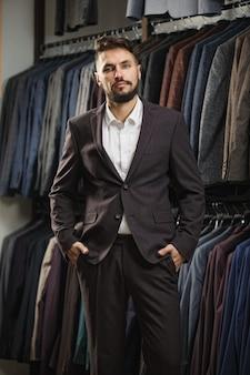 Jovem elegante de terno escolhendo terno em shopping ou loja de roupas