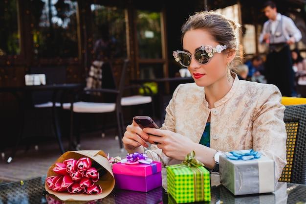 Jovem elegante e bonita na moda, óculos de sol, sentada num café, segurando o telefone