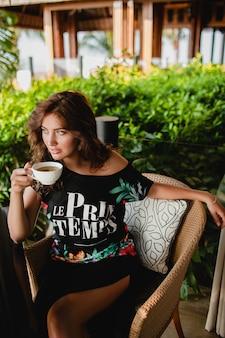 Jovem elegante e bonita sentada em um café de resort tropical