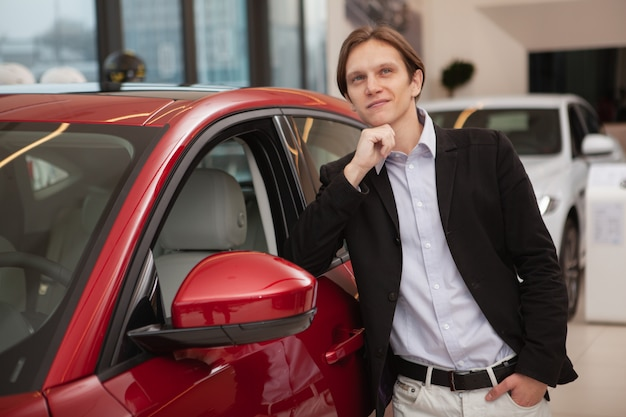 Jovem elegante e charmoso olhando para o outro lado com ar sonhador, apoiando-se em um carro novo na concessionária de automóveis