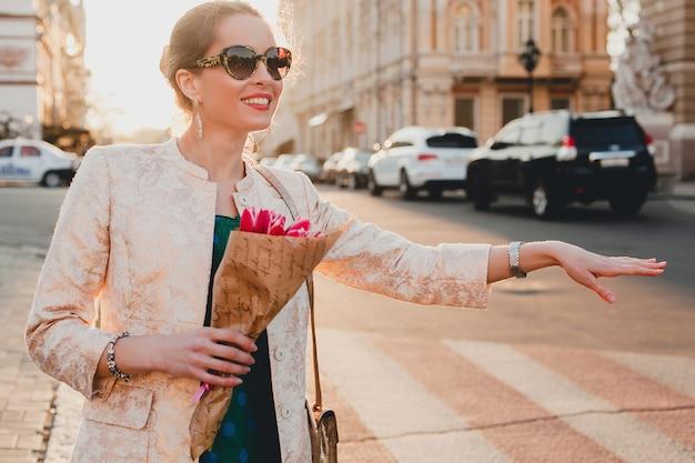Jovem elegante e linda mulher caminhando na rua ao pôr do sol, pegando um táxi