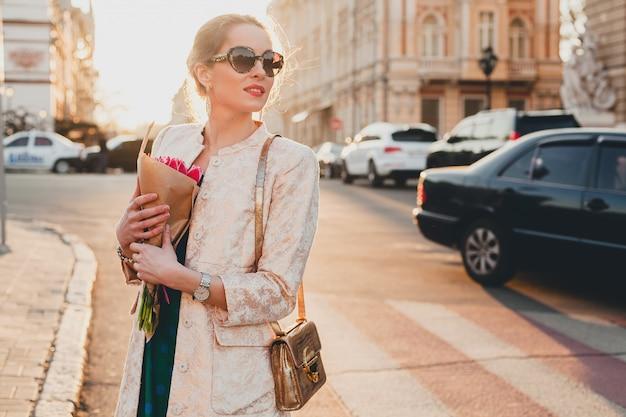 Jovem elegante e linda mulher caminhando na rua ao pôr do sol