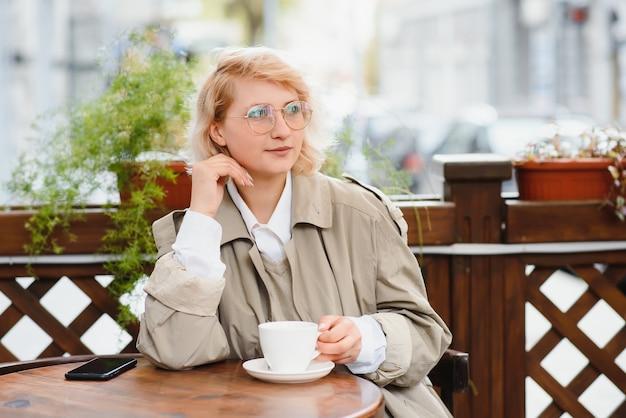 Jovem elegante e linda mulher sentada em um café da cidade na rua