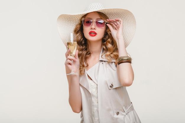Jovem elegante e sorridente loira com um grande chapéu e óculos escuros segurando uma taça de champanhe em uma festa feliz