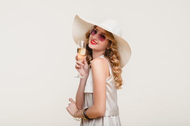 Jovem elegante e sorridente loira com um grande chapéu e óculos escuros segurando uma taça de champanhe