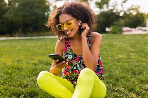 Jovem elegante e sorridente mulher negra usando smartphone e ouvindo música em fones de ouvido sem fio se divertindo no parque