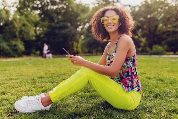Jovem elegante e sorridente mulher negra usando smartphone, ouvindo música em fones de ouvido sem fio, se divertindo no parque, estilo colorido da moda do verão, sentada na grama, óculos de sol amarelos
