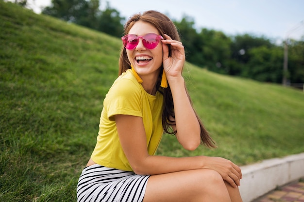 Jovem elegante e sorridente se divertindo no parque da cidade, sorrindo, alegre, vestindo blusa amarela, minissaia listrada, óculos de sol rosa, tendência da moda no estilo de verão