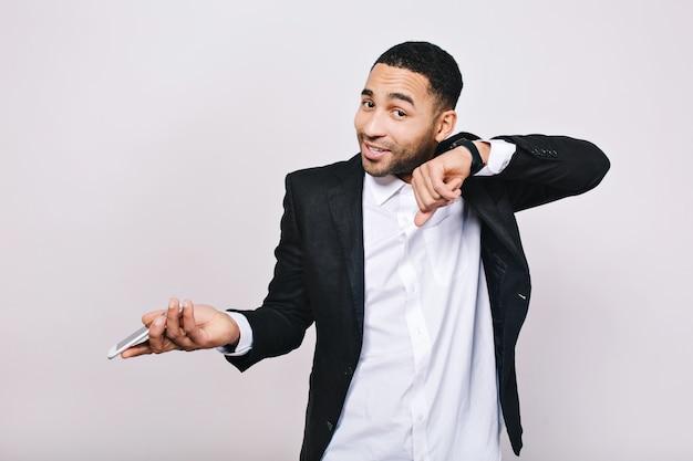 Jovem elegante em camisa branca e jaqueta preta se divertindo com o telefone e o relógio. empresário, trabalho, reunião, bom humor, sorrindo