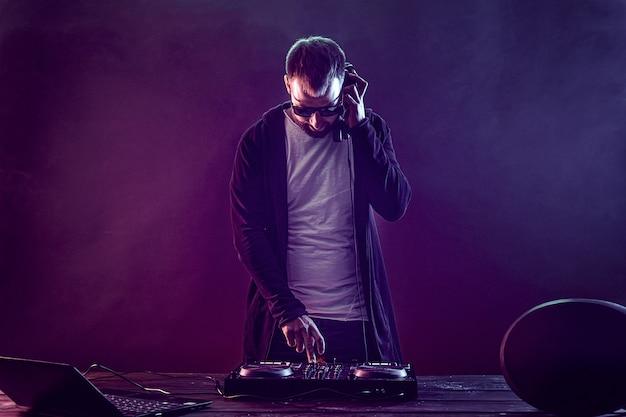Jovem elegante em copos posando atrás de console de mixagem no estúdio de fumaça colorida