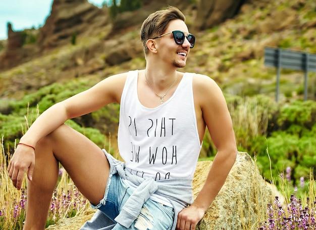 Jovem elegante em roupas casuais hipster posando na natureza