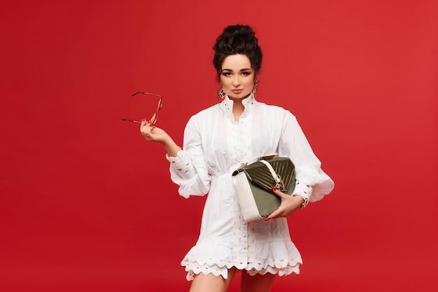 Jovem elegante em um vestido branco e óculos escuros da moda, posando com uma bolsa dourada sobre costas vermelhas.