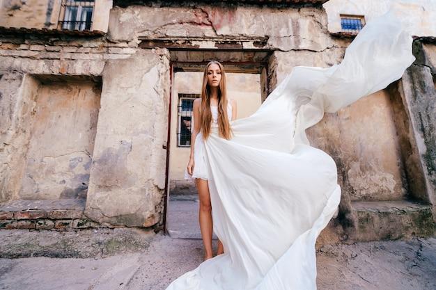 Jovem elegante em um vestido branco esvoaçante posando sobre edifícios antigos de pedra
