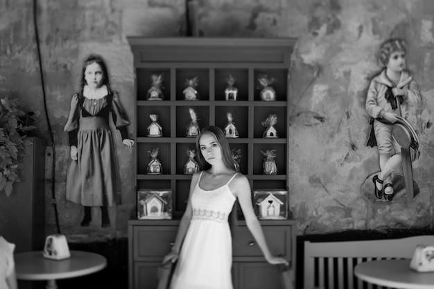 Jovem elegante em um vestido branco posando sobre uma parede decorada