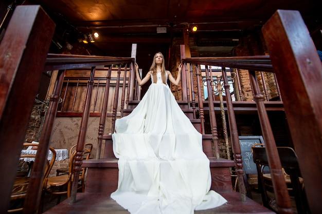 Jovem elegante em um vestido longo branco esvoaçante, posando na escada interna