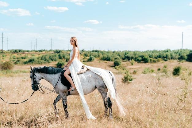 Jovem elegante em um vestido longo branco esvoaçante, posando no cavalo na zona rural