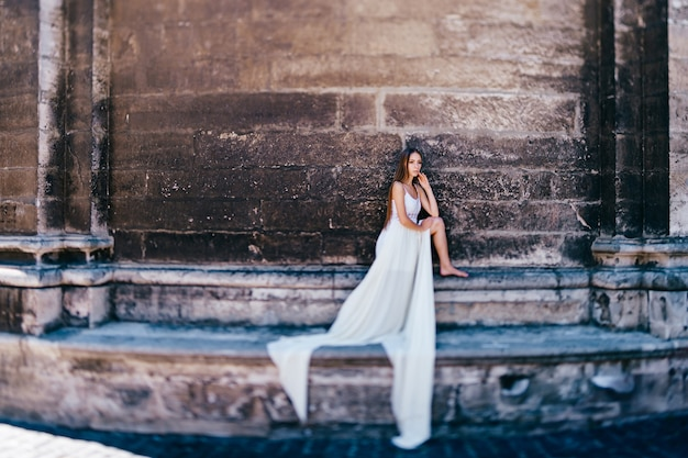 Jovem elegante em um vestido longo branco esvoaçante posando sobre uma parede de pedra antiga