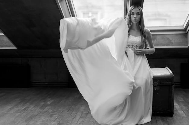 Jovem elegante em um vestido longo branco flutuante sentada no baú dote no loft