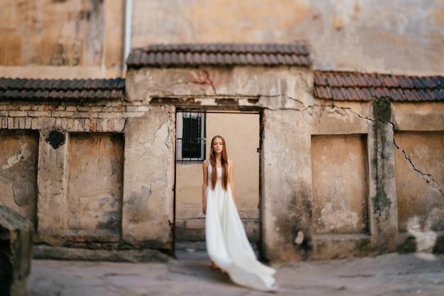 Jovem elegante em um vestido longo branco posando sobre edifícios antigos de pedra