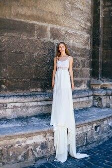 Jovem elegante em um vestido longo branco posando sobre um muro de pedra