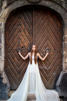 Jovem elegante em um vestido longo branco posando sobre uma porta antiga