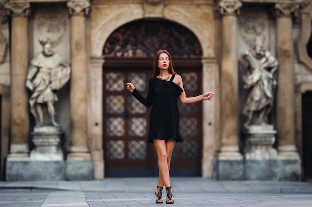 Jovem elegante em um vestido preto em estilo urbano nas ruas da cidade de brno. checo.