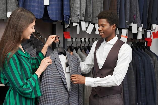 Jovem elegante, escolhendo a jaqueta cinza na boutique.