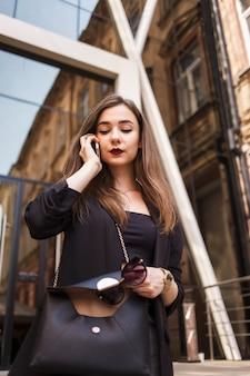 Jovem elegante falando ao telefone perto do prédio de escritórios. mulher de negócios, falando ao telefone, colocando os óculos em sacos