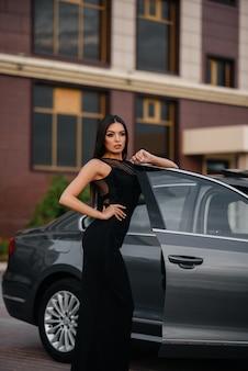 Jovem elegante fica perto do carro em um vestido preto. moda e estilo de negócios