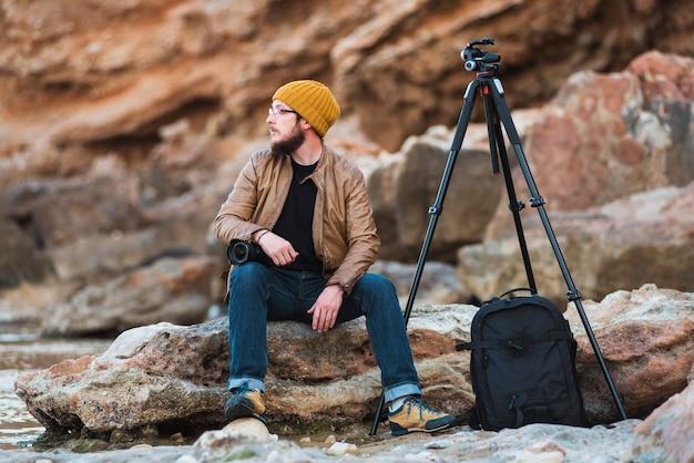 Jovem, elegante, fotógrafo, com, câmera, sentando, ligado, rocha, e, olhando mar