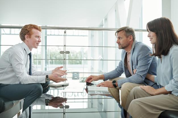 Jovem elegante gerente do centro automotivo sentado na frente de clientes e explicando-lhes os termos e condições de compra de um carro novo