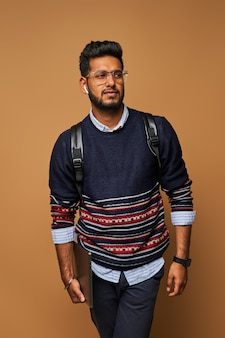 Jovem elegante handome indiano com mochila e laptop em copos na parede.