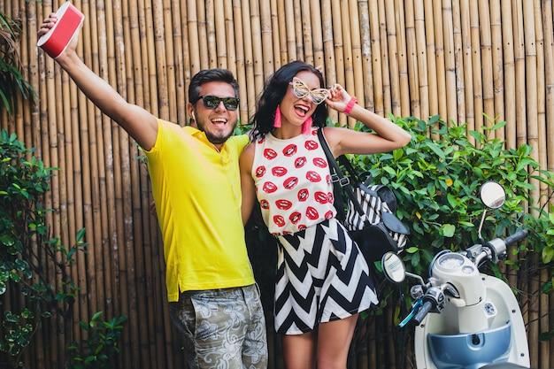 Jovem elegante hippie lindo casal nas férias de verão na tailândia, glamour, roupas de tendências da moda, óculos de sol, férias tropicais, romance de férias, sorrindo, feliz, ouvindo música, festa, dança