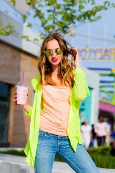 Jovem elegante hippie loira com óculos de sol e coquetel posando ao ar livre