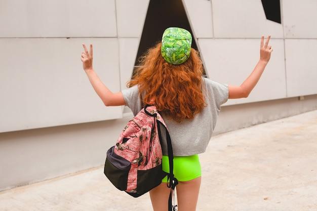 Jovem elegante hippie ruiva, caminhando na rua, boné verde, roupas da moda, roupa da moda, estilo adolescente urbano, mochila, viajante, vista de trás, mostrando o símbolo da paz, viajando na ásia