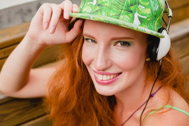 Jovem elegante hipster feliz mulher ruiva, ouvindo música, fones de ouvido, boné verde, sorrindo, cara engraçada de perto, se divertindo, humor louco, estilo urbano