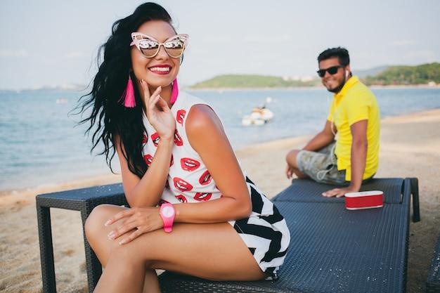 Jovem elegante hipster linda mulher sentada na praia, glamour, sexy, quente, roupa da moda, óculos de sol da moda, férias tropicais, romance de férias, lua de mel, homem no fundo, olhando, sorrindo, feliz
