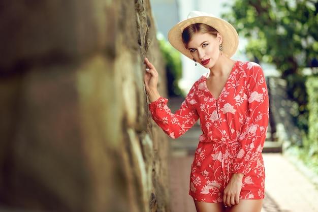 Jovem elegante linda garota sexy em um terno vermelho e um chapéu fica perto de uma parede de tijolos