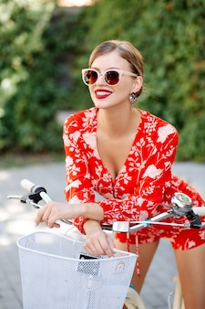 Jovem elegante linda garota sexy em um terno vermelho no verão em uma cidade usando óculos escuros, andando de bicicleta
