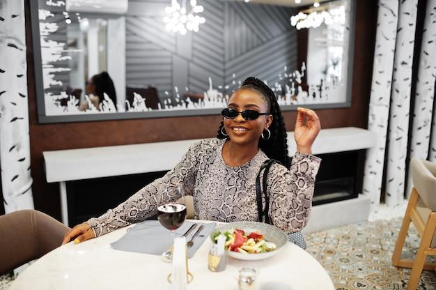 Jovem elegante mulher afro-americana, usa óculos escuros pretos, sentada no restaurante, desfrutando de uma comida saudável com vinho.