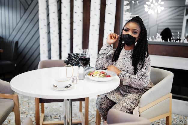 Jovem elegante mulher afro-americana, usando máscara preta, sentada no restaurante, desfrutando de uma comida saudável com vinho.