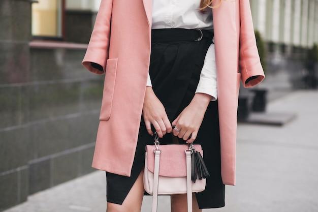 Jovem elegante mulher bonita andando na rua, vestindo um casaco rosa, segurando uma bolsa, saia preta, roupa da moda, tendência de outono, acessórios, close-up de mãos, detalhes