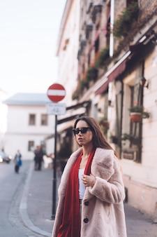 Jovem elegante mulher bonita andando no casaco rosa