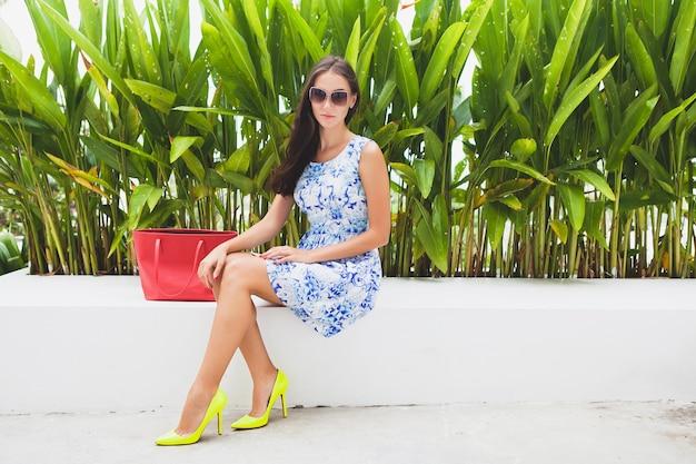 Jovem elegante mulher bonita em vestido estampado azul, bolsa vermelha, óculos de sol, bom humor, roupa da moda, roupas da moda, sorrindo, sentada, verão, sapatos de salto alto amarelos, acessórios