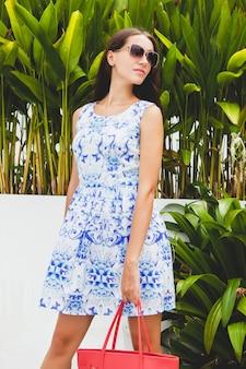 Jovem elegante mulher bonita em vestido estampado azul, bolsa vermelha, óculos de sol, bom humor, roupa da moda, roupas da moda, sorrindo, verão, acessórios