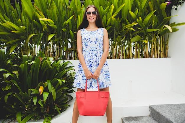 Jovem elegante mulher bonita em vestido estampado azul, bolsa vermelha, óculos de sol, roupa da moda, roupas da moda, sorrindo, sentada, verão, acessórios