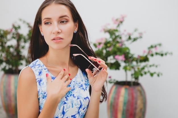 Jovem elegante mulher bonita em vestido estampado azul, óculos de sol, bom humor, roupa da moda, roupas da moda, sorrindo, verão, acessórios
