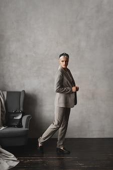 Jovem elegante mulher de negócios em um terno moderno, posando no interior de um apartamento vintage vazio.