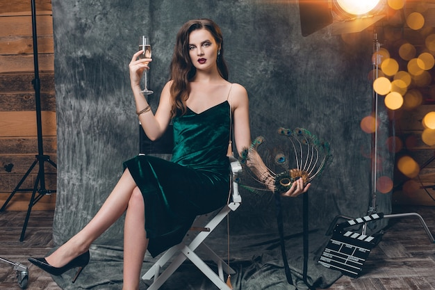 Jovem elegante mulher sexy sentada em uma cadeira nos bastidores do cinema, comemorando com uma taça de champanhe